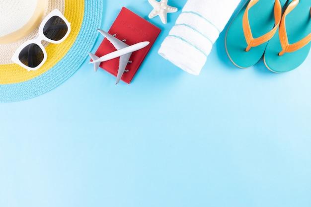 ビーチ帽子、サングラス、タオル、パスポート、明るい青の背景にフリップフロップ。夏や休暇。