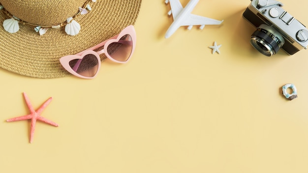 Beach hat with camera and travel items on yellow background, summer vacation concept