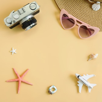 Beach hat with camera and travel items on yellow background