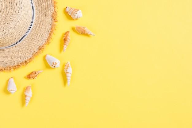 갈색 노란색 테이블에 조개와 비치 모자입니다.