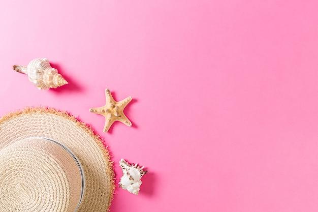 ピンクの木製テーブルに貝殻のビーチ帽子。コピースペースの上面図と夏の背景の概念。