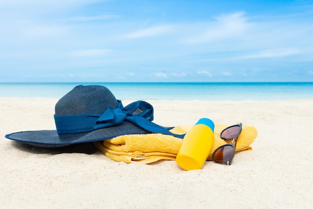 Beach hat with sunblock lotion bottle and sunglasses on yellow towel
