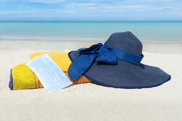 タオルと砂の上の医療マスクとビーチハット。