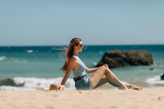 Пляжные каникулы женщина вид сзади наслаждаясь летним солнцем, сидя в песке, глядя счастливым на пространство копии. красивая молодая модель