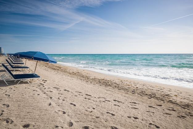 Пляж в майами, флорида. открытые зонтики на песчаном пляже у океана. пустой пляж. берег моря. раннее утро. фон облака.