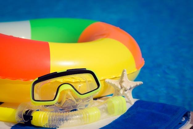 青い水を背景にビーチアイテム夏休みのコンセプト
