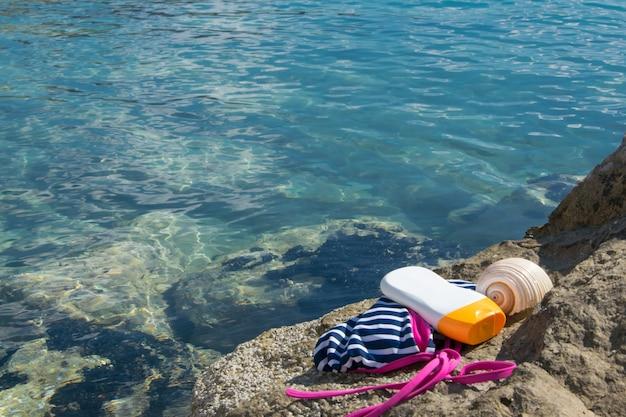 해변 항목 수영복 태양 보호 크림과 해변 바위에 조개