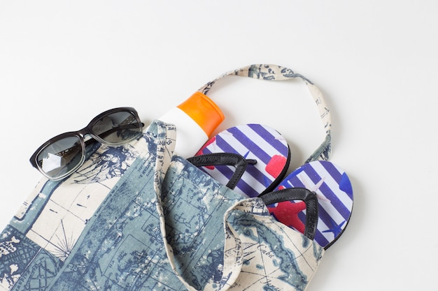 Beach items with  flip flops, cream,  sunglasses, top view. vacation concept with marine theme