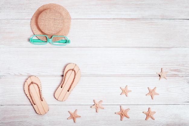 여름 신발, 모자, 불가사리, 흰색 나무 표면에 선글라스와 해변 라운지 공간