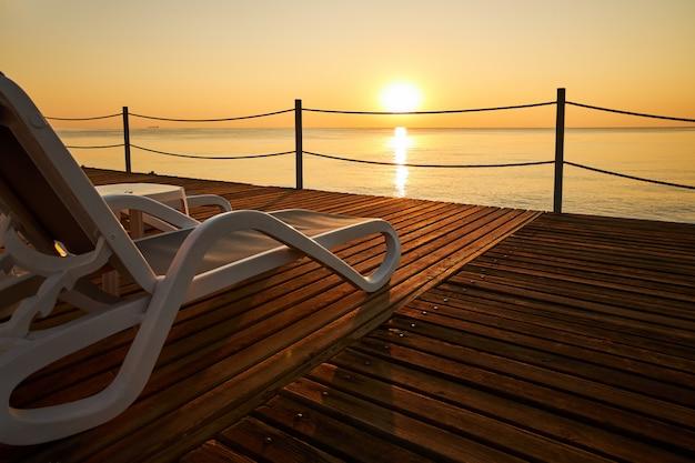Пляжный шезлонг стоит на деревянном пирсе на фоне спокойного моря и восходящего солнца
