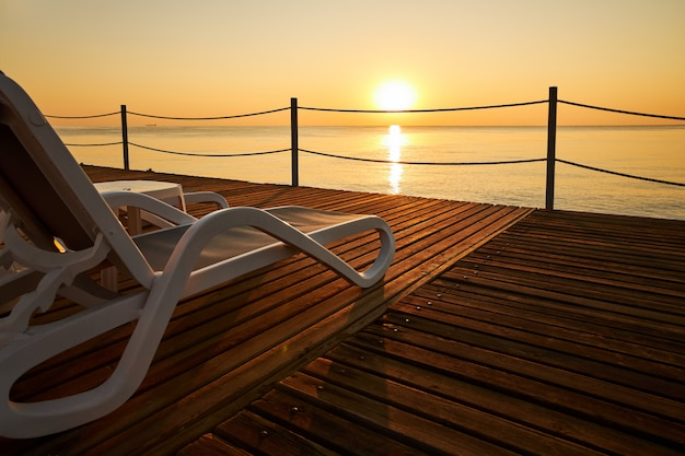 Beach lounger stands on a wooden pier against the background of a calm sea and the rising sun