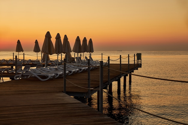 Beach loungers and umbrellas stand on a wooden pier in the early morning waiting for vacationers