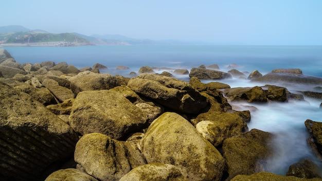 スペイン北部の霧と長時間露光の大きな岩のビーチ。バスク。
