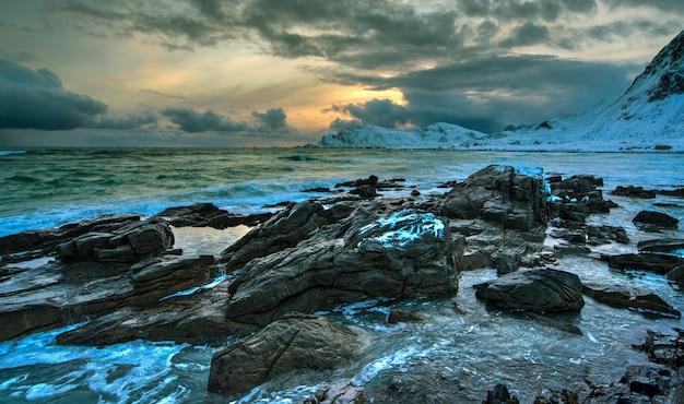Пляж норвежского моря на скалистом берегу на закате зимой