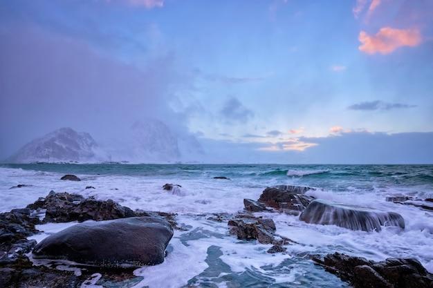 Пляж норвежского моря на скалистом побережье фьорда на закате зимой. пляж варейд.