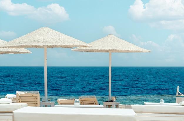 호텔 리조트의 해변, 아름다운 바다를 배경으로 비치 파라솔 및 일광욕용 라운저