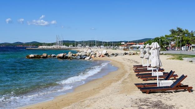 닫힌 우산과 선베드가있는에게 해 연안의 해변, 물 근처의 바위, 제방 거리, 바다 항구 및 nikiti, 그리스의 거리에있는 푸른 언덕