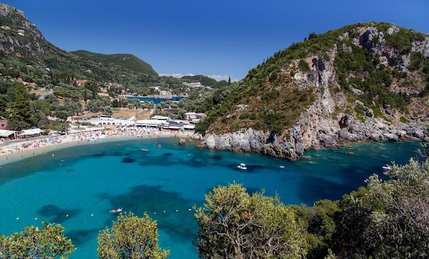 Пляж палеокастрица на острове корфу, греция. туристы наслаждаются приятным летним отдыхом.