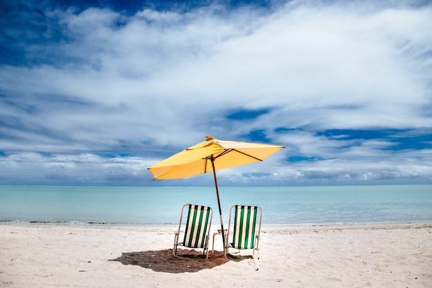 Пляжный зонтик и зеленые шезлонги на берегу