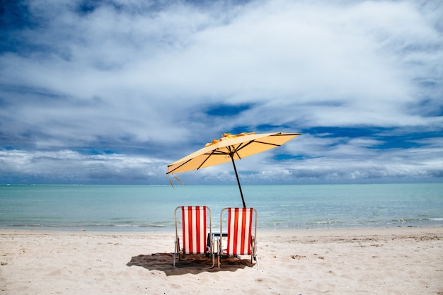 Beach parasol and red beach chairs on a shore