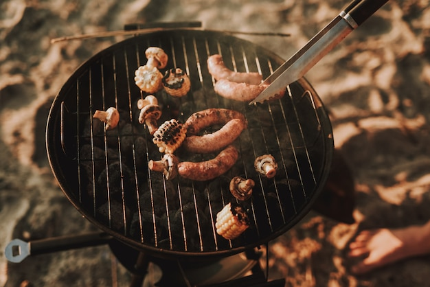 Beach party concept. man grills barbecue sausages.