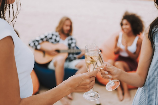 Beach party guitar playing champagne drinking.