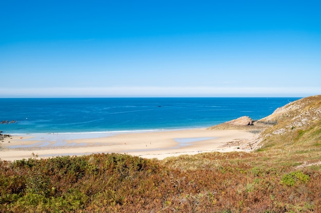 Beach pit on breton coastline in france frehel cape region with its sand, rocks and moorland in summer