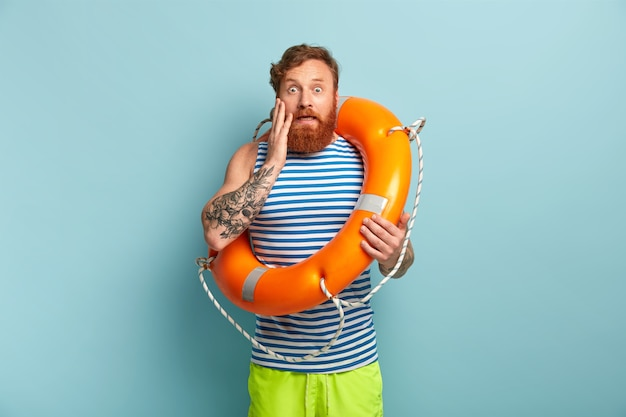 Lifebuoy와 함께 포즈를 취하는 해변 보호 남성