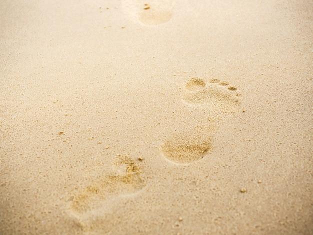 복사 공간이 있는 해변 모래 발자국. 모래 해변 배경에서 맨발로 걷는 인간의 발자국을 닫습니다. 여행, 여름 배경 개념입니다.