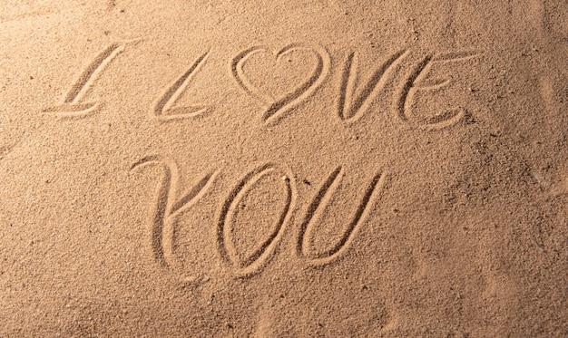 砂に書かれたロマンチックなフレーズとビーチの砂