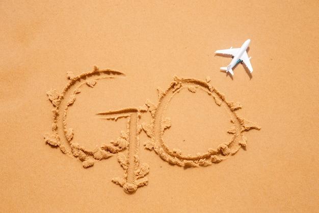 옆에 장난감 비행기와 함께 '가라'라고 쓰여진 해변 모래. 여행 컨셉
