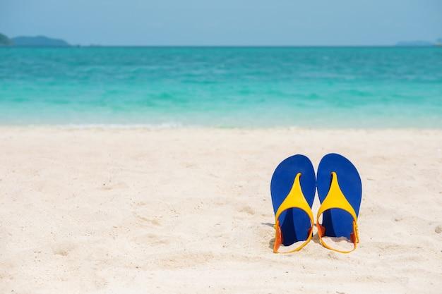 Beach sandals on the sandy sea coast, summer concept holiday