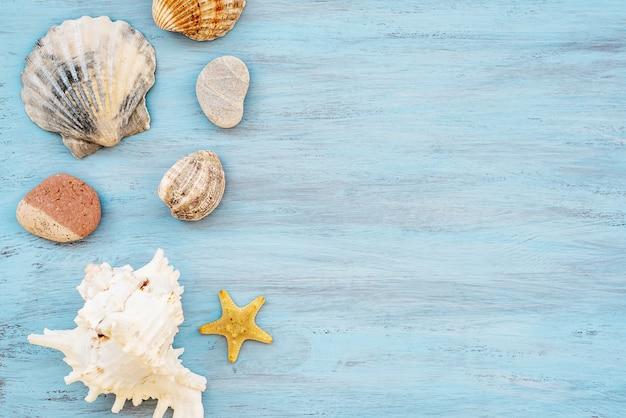 海の貝殻や青い木製の背景にヒトデのビーチシーンのコンセプト