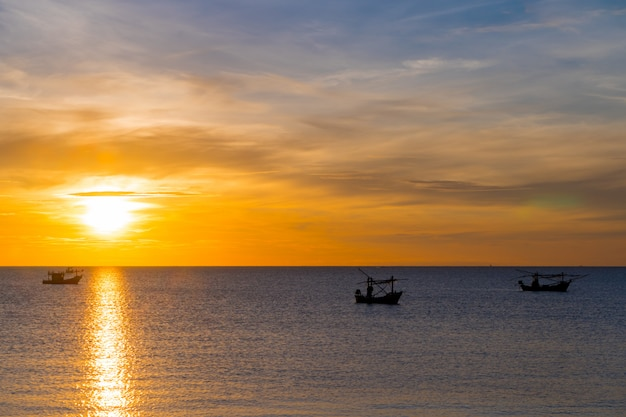 Beach, sea during the summer season in the morning sunrise with silhouette fishing boat.