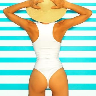 ビーチシームード。スタイリッシュな白い水着とビーチアクセサリーの女の子