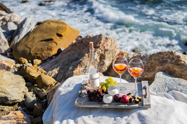 Beach sea scene summer picnic with rose wine and grapes, marshmallow, berries.