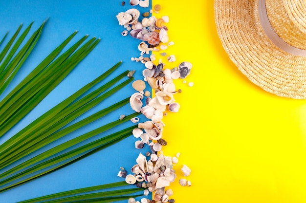 Beach sea vacation concept composition hat, palm leaf, sea shell on blue, yellow color . close up. top view. selective soft focus. text copy space.