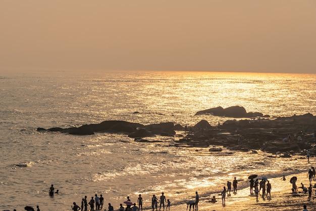 The beach under the setting sun is golden.