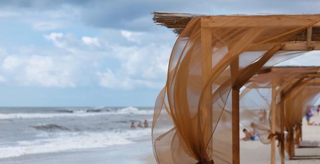 해변은 바람에 나부끼고있는 갈색 커튼으로 흘린다.