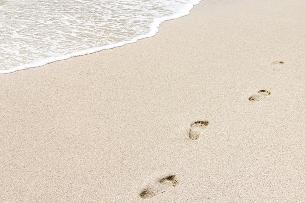 Beach shore with footprints in cloudy day