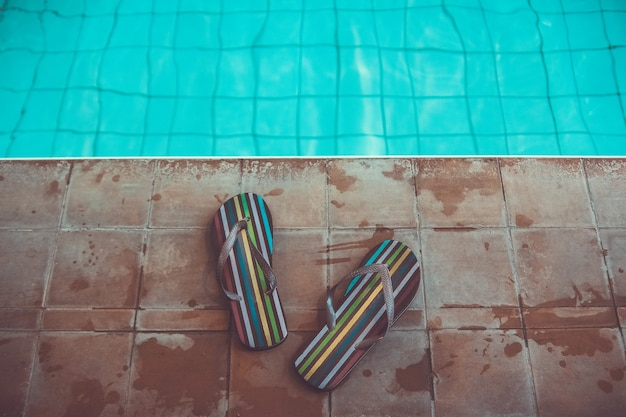 Beach slippers stripped flip flops near sport swimming pool with blue water