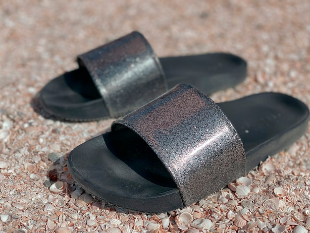 Beach slippers with black soles and shimmery silver upper stand close-up on a pebble beach.