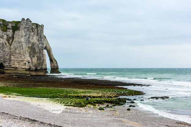The beach and stone cliffs in etretat, france