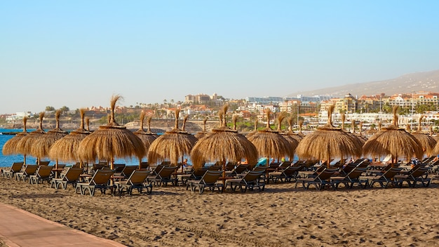 Beach straw umbrellas at sunset landscape.
