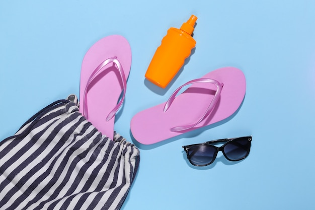Beach striped bag with accessories on blue. beach vacation concept.