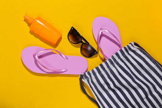 Beach striped bag with accessories on a yellow. beach vacation concept.