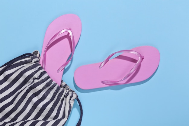Beach striped bag with flip flops on blue. beach vacation concept.
