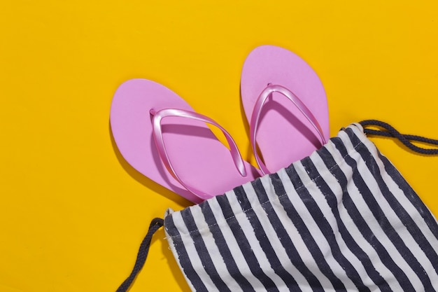 Beach striped bag with flip flops on a yellow. beach vacation concept.