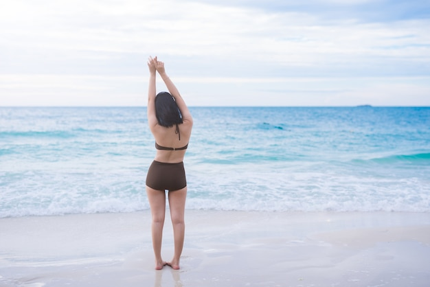 Beach summer holidays woman in happy freedom concept with arms raised out in happiness.
