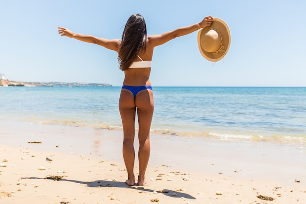 Beach summer holidays woman in happy freedom concept with arms raised out. latin sexy woman wearing white bikini with straw hat in hands